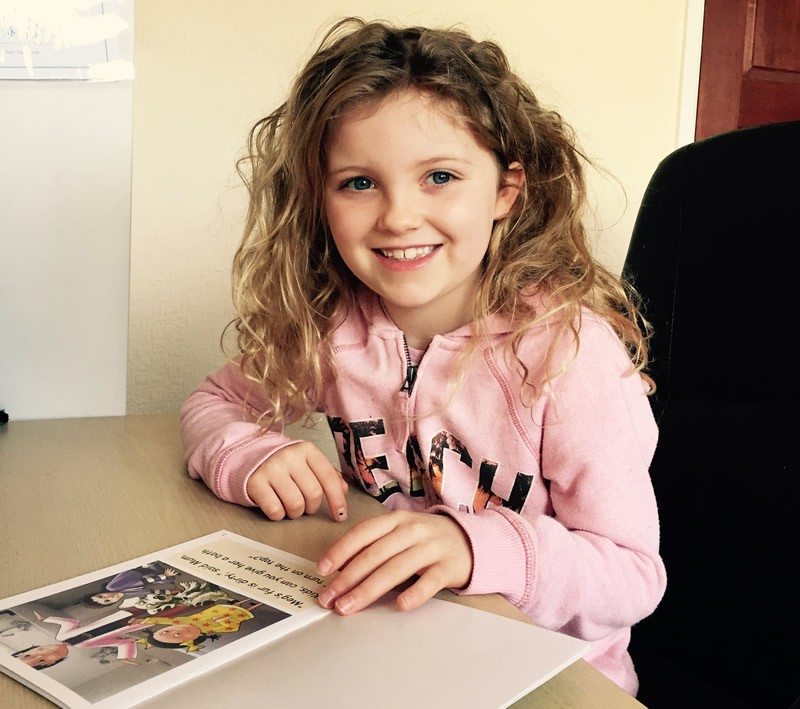 Girl smiling and reading story book