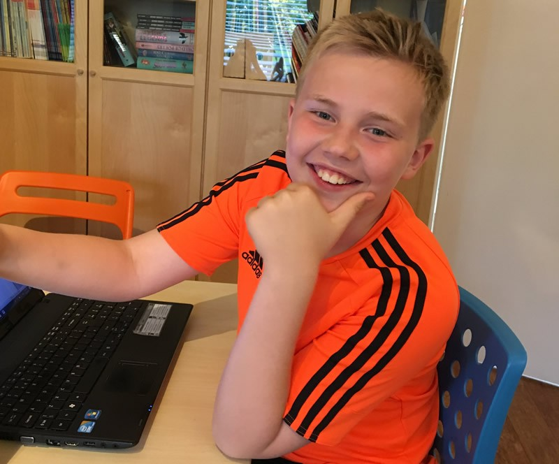 Boy in orange shirt smiling and using laptop