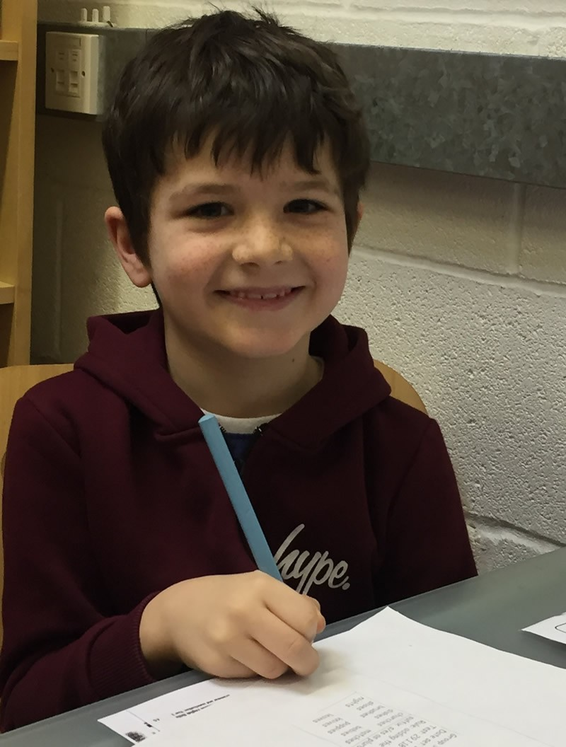 Boy in purple hoodie smiling and writing