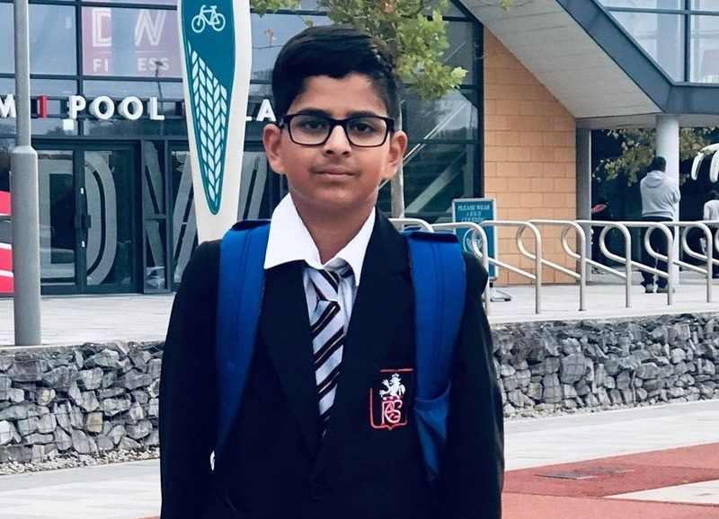 11+ student in school uniform standing outside