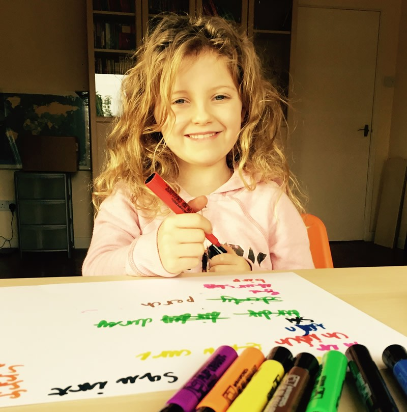 Girl smiling and using coloured pens
