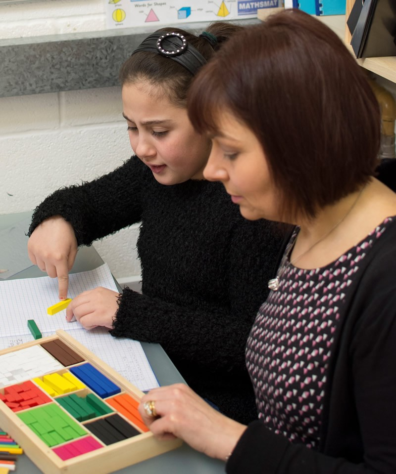 Andrea sat with student who is using coloured blocks during a tuition session