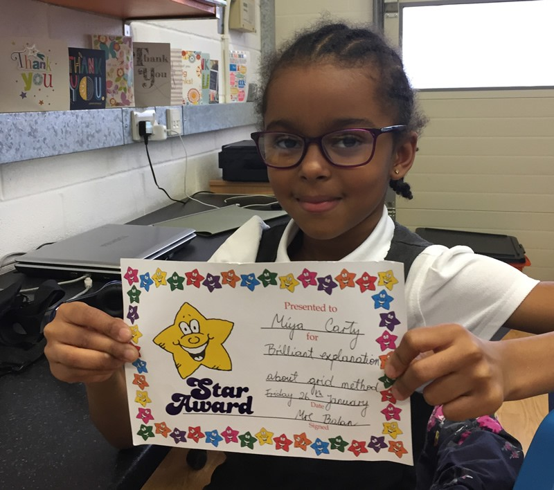 Girl with glasses proudly holding Aspire Star Award