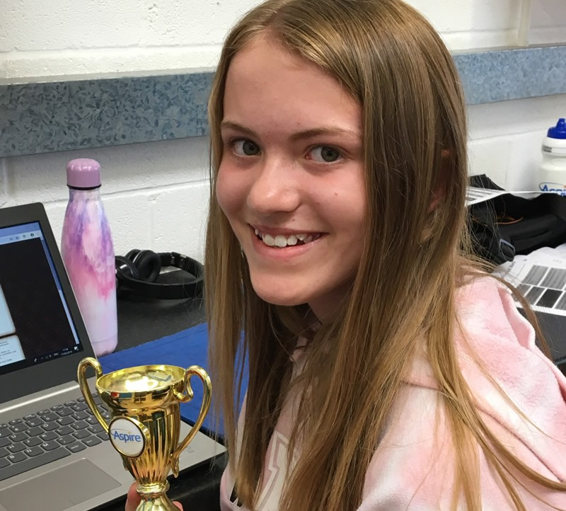 Girl proudly showing her Aspire Tuition gold award trophy