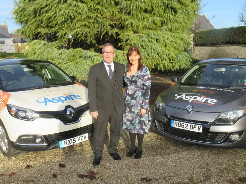 David and Andrea stood next to cars with Aspire logos and branding