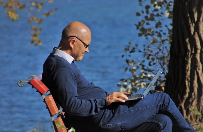 Man sat by lake samiling thoughtfully while viewing his laptop